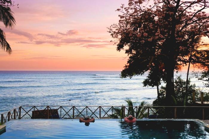 Plano de dos amigos disfrutando de una espectacular puesta de sol dentro de la piscina infinita del hotel Santa Catalina
