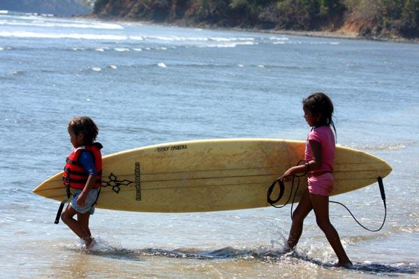 Niños cargando una tabla de surf