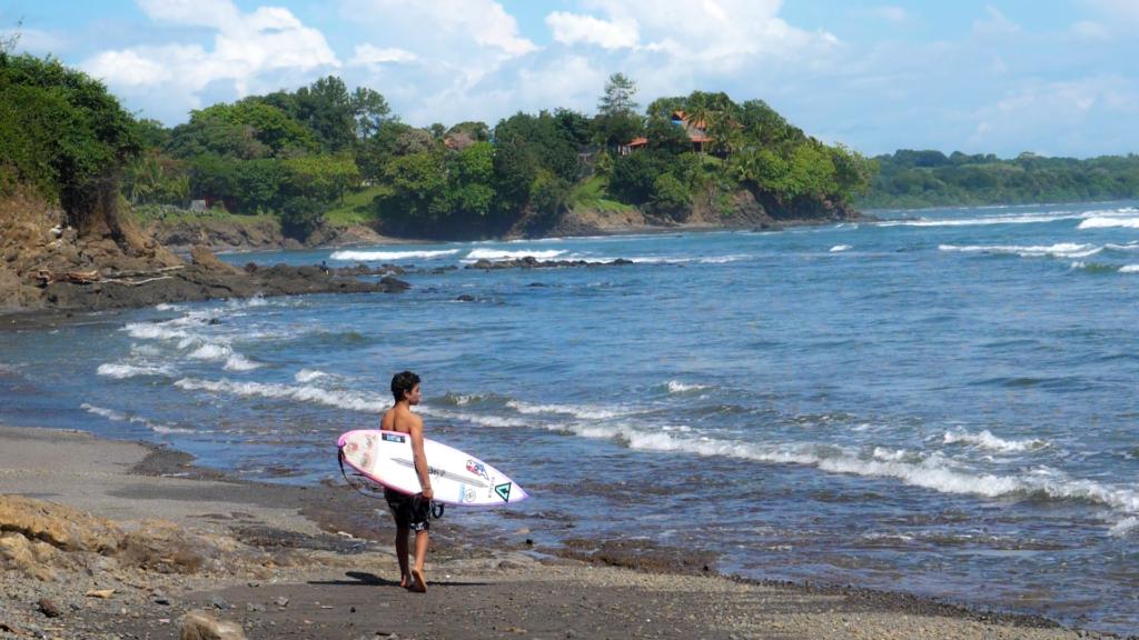 Surfista mirando las olas con la tabla en la mano esperando para entrar al agua