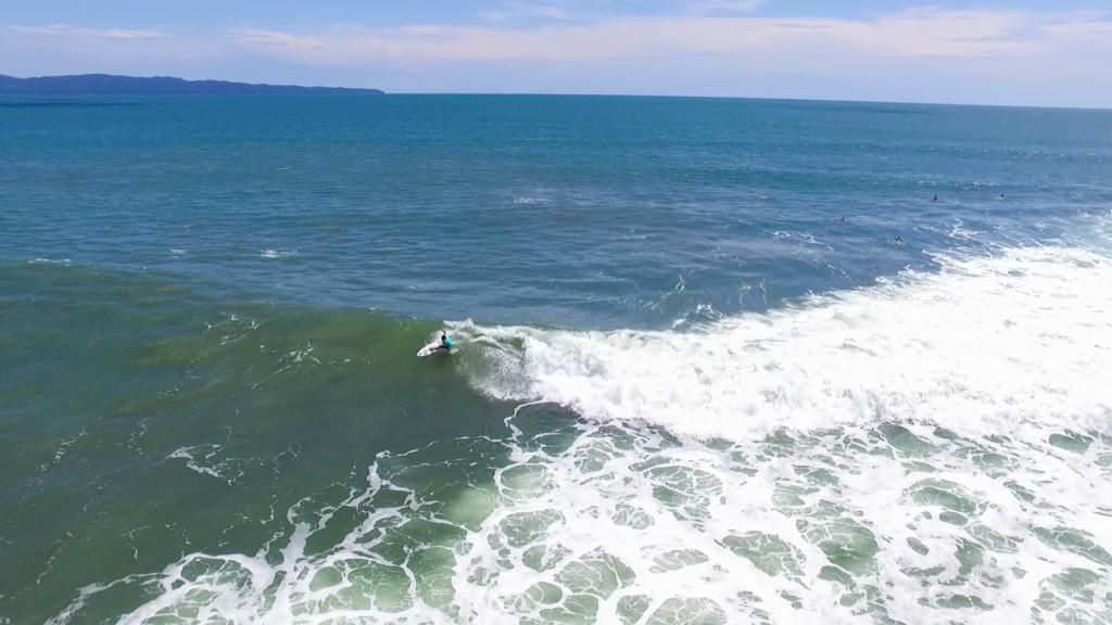Plano desde arriba de un surfista cabalgando las olas
